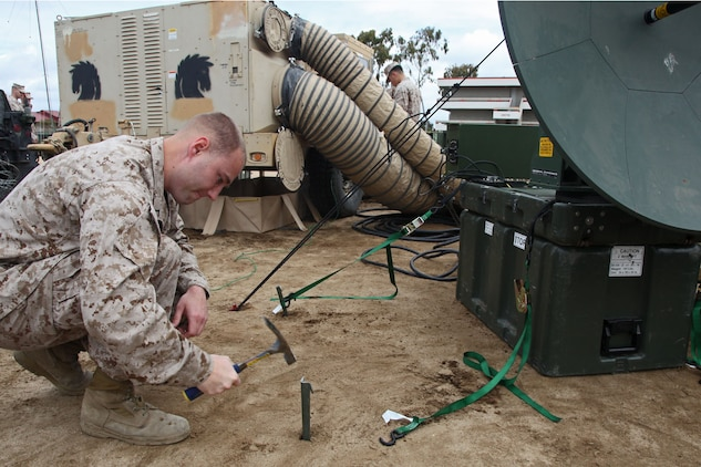 Pfc. Christopher S. Lafriniere, data communications specialist, Battalion Landing Team 3/5, 15th Marine Expeditionary Unit, drives a stake to secure a Support Wide Area Network satellite during a Communications Exercise with the entire Marine Air Ground Task Force at Camp Delmar, March 19. The five-day training exercise is meant to prepare the 15th MEU for a deployment qualification exercise in the coming future.