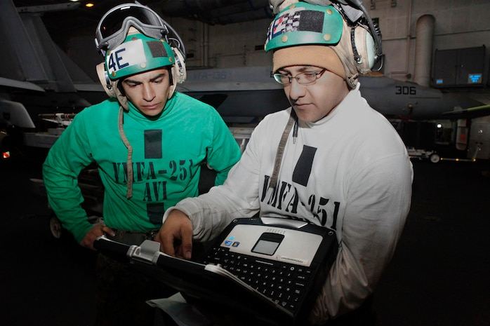 Lance Cpl. Joshua Ochoa, left, and Cpl. Victor Castellanos, Marine Fighter Attack Squadron 251 avionics technicians, review a circuit board diagram while aboard aircraft carrier USS Enterprise, March 19. The laptops allow the Marines to download various diagrams to increase job proficiency.