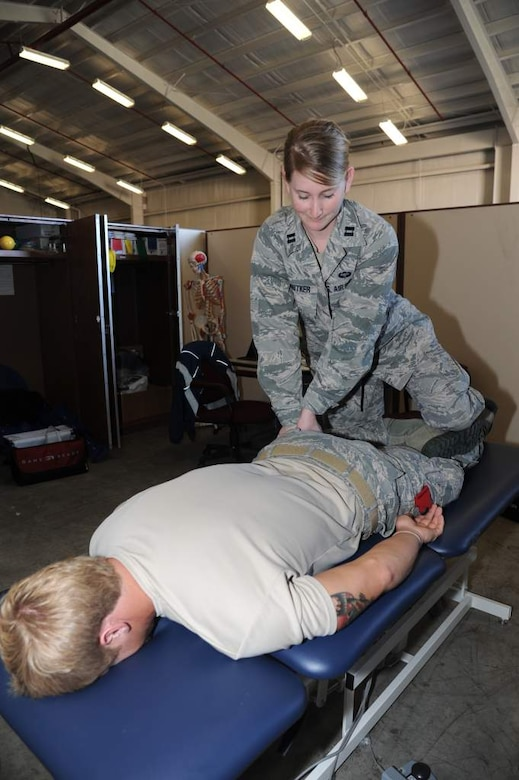 Capt. Danielle Schnitker, 23rd Special Tactics Squadron physical therapist, stretches the leg muscles of a combat controller assigned to the 23rd STS. Schnitker mainly works on combat related injuries providing daily physical therapy to help with recovery, lower injury rates and ensure Airmen are deployment ready. (U.S. Air Force photo by Master Sgt. Steven Pearsall)
