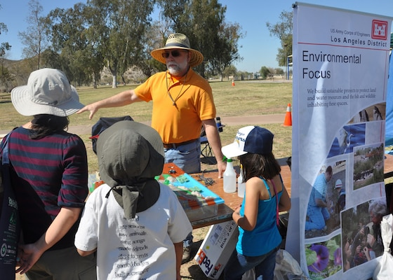 Vic Bartkus, a U.S. Army Corps of Engineers Los Angeles District team member, speaks with a family Mar. 10 about the District's involvement in ecosystem restoration at the annual Tres Rios Nature and Earth Festival held in Goodyear, Ariz. The festival draws in government agencies and organizations from across Arizona interested in promoting awareness of the history and habitat in the Phoenix area.