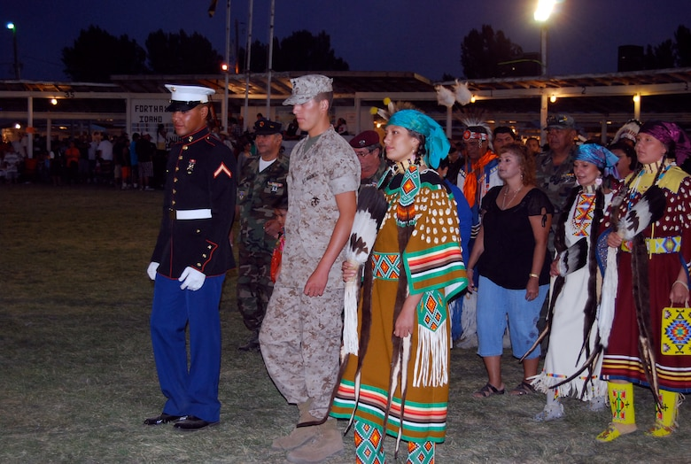 "Marine Cpl. Rodrick Timbana, left, joins Staff Sgt. Brittinie Alvarez, far right, in traditional native Shoshoni dress, and her brother, Marine Cpl. Blake ""Sonny"" F. Alvarez, center, as they lead a Grand Entry Ceremony on their reservation in Idaho. (courtesy photo)"