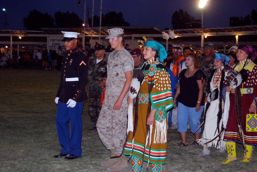 """Marine Cpl. Rodrick Timbana, left, joins Staff Sgt. Brittinie Alvarez, far right, in traditional native Shoshoni dress, and her brother, Marine Cpl. Blake """"Sonny"""" F. Alvarez, center, as they lead a Grand Entry Ceremony on their reservation in Idaho. (courtesy photo)"""
