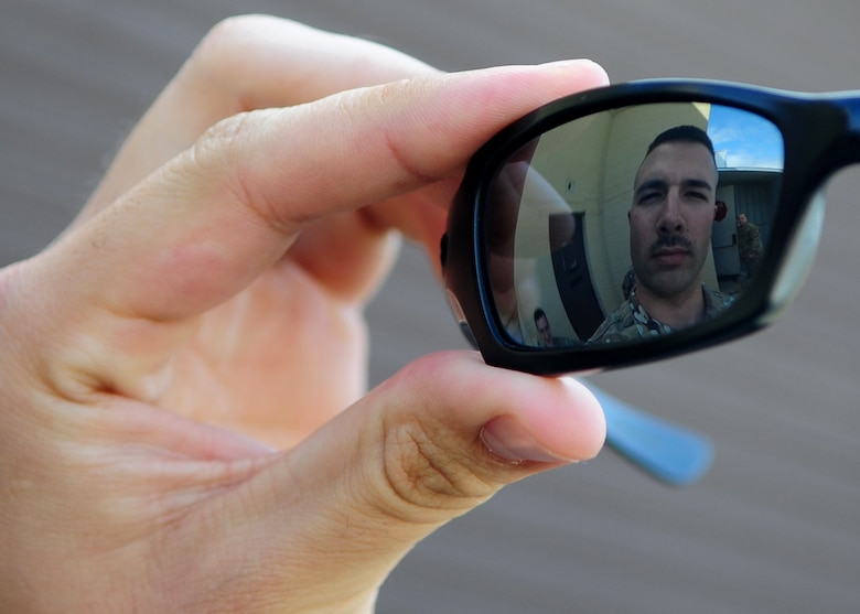 Staff Sgt. Kenneth Nelson, 9th Munitions Squadron technician, looks at his mustache in his sunglasses during a work break at the Beale AFB, Calif.,  bomb dump March 12, 2012. Many Airmen are growing mustaches in observance of Mustache March, which may have been started by Retired U.S. Air Force Brig. General Robin Olds. (U.S. Air Force photo by Senior Airman Shawn Nickel/Released)