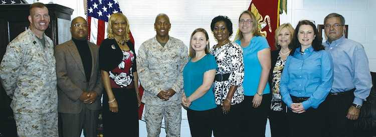 Employees, who work with the base's youth programs, are recognized by Col. Terry V. Williams, center, commanding officer, Marine Corps Logistics Base Albany, and Sgt. Maj. Conrad E. Potts, far left, sergeant major, MCLB Albany, for their performance on a multi-disciplinary inspection, March 15.