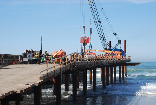 A crane and other construction equipment sit atop the temporary pier built to construct the westernmost segment of the border fence that separates Mexico and the United States. The pier enabled the contractor to overcome obstacles unique to working in a surf zone.