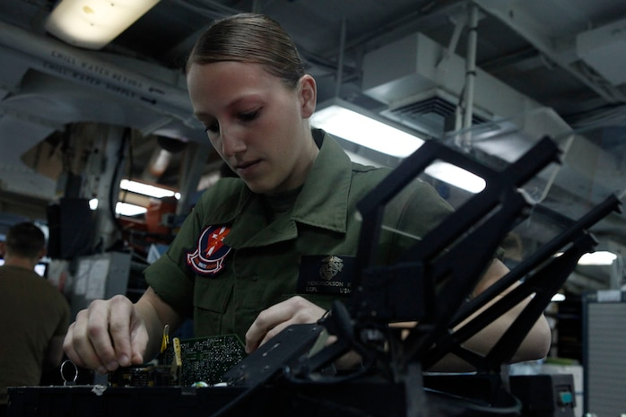Lance Cpl. Karissa Hendrickson, Marine Fighter Attack Squadron 251 Consolidated Automated Support System technician, takes apart a heads-up display system aboard the aircraft carrier USS Enterprise, March 24. Various shops are present in the avionics branch to provide support for aircraft aboard the carrier.