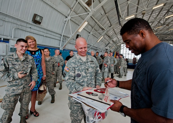 Sgt. 1st Class Matthew Talley, of the 719th Contingency Contracting Team, gets Herschel Walker to sign his 1983 Georgia Bulldogs pennant March 22 at Eglin Air Force Base, Fla.  Walker visited the base to speak about resiliency and the importance of asking for help. He spoke twice to large crowds of Team Eglin members about his life, career and the emotional and mental struggles he encountered throughout.  (U.S. Air Force photo/Samuel King Jr.)