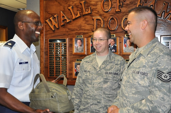 """Chaplain, Lt. Col. Calvin Dixon (left) offers candy to Tech. Sgt. Sean Phillips (center) and Tech. Sgt. Ryan Von Oven (right), both Noncommissioned Officers-in-Charge of Network Operations at the Air Force Technical Applications Center.  The chaplain was making his rounds to AFTAC Airmen as part of his pastoral visits to the organization.  """"Successful religious programs are ones that meet people's needs,"""" Dixon said.   (U.S. Air Force photo by Susan A. Romano)"""
