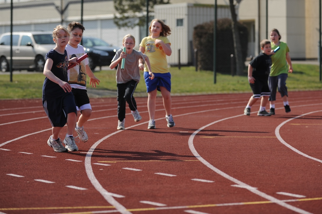 BITBURG ANNEX, Germany – Spangdahlem and Bitburg Elementary and Middle School students hand off batons during the 400-meter relay during a track and field day at the Bitburg High School track here March 24. The BHS track team hosted the event to introduce the first- through sixth-grade students to the sport's events. The team taught students about track and field to promote interest in staying active and healthy. (U.S. Air Force photo by Airman 1st Class Matthew B. Fredericks/Released)