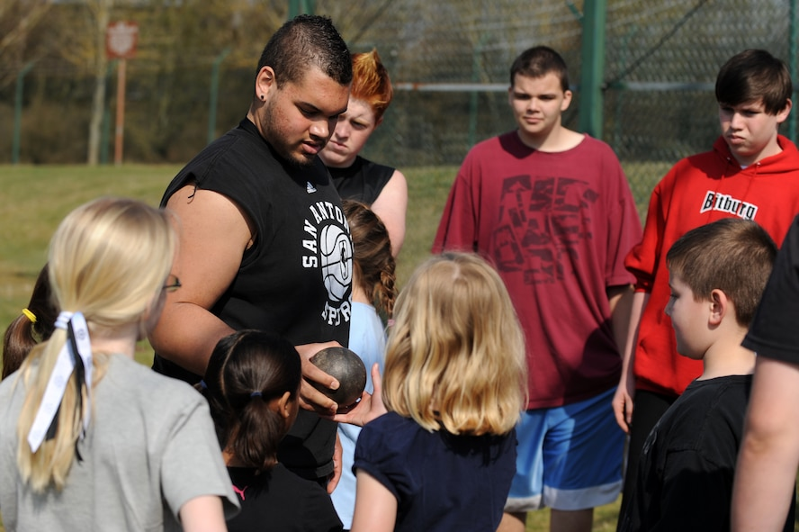 BITBURG ANNEX, Germany – Colton Engelmeier, son of Master Sgt. Eric Hall, 52nd Communications Squadron, shows the metal ball used in shot put to Spangdahlem and Bitburg Elementary and Middle School students during a track and field day at the Bitburg High School track here March 24. The BHS track team hosted the event to introduce the first- through sixth-grade students to the sport's events. The team taught students about track and field to promote interest in staying active and healthy. (U.S. Air Force photo by Airman 1st Class Matthew B. Fredericks/Released)