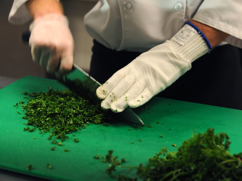 Senior Airman Brady McDede, 6th Force Support Squadron food service technician, chops parsley to be used in Manhattan clam chowder, at the Citi Bank corporate building in Tampa, Fla., March 23, 2012. McDede was sent by 6th FSS to train with civilan chefs to help improve the dining conditions on MacDill Air Force Base, Fla. (U.S. Air Force photo by Airman Basic David Tracy)