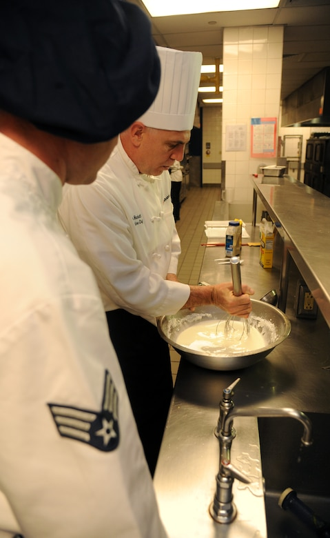 Senior Airman Brady McDede, 6th Force Support Squadron food service technician, observes stirring techniques performed by Executive Chef, John Hackett, at the Citi Bank corporate building in Tampa, Fla., March 23, 2012. McDede was sent by 6th FSS to train with civilan chefs to help improve the dining conditions on MacDill Air Force Base, Fla. (U.S. Air Force photo by Airman Basic David Tracy)