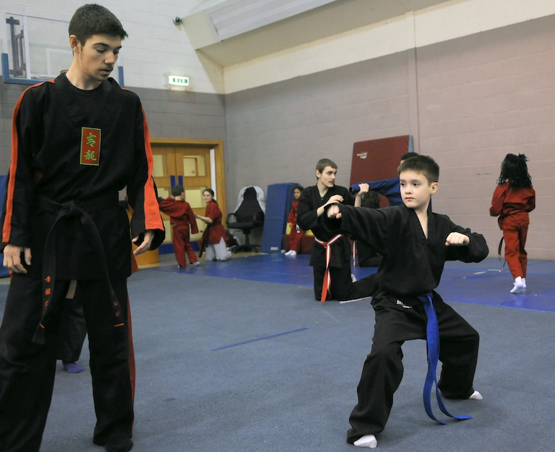 RAF MILDENHALL, England -- Daniel McCollum  checks the form of Duncan Norwood's punching ready stance during the RAF Mildenhall Youth Center's Karate Camp March 15, 2012. As an advanced student in the martial arts class, McCollum assists the instructor with small group exercises and gives advice to other students. (U.S. Air Force photo/Staff Sgt. Thomas Trower)