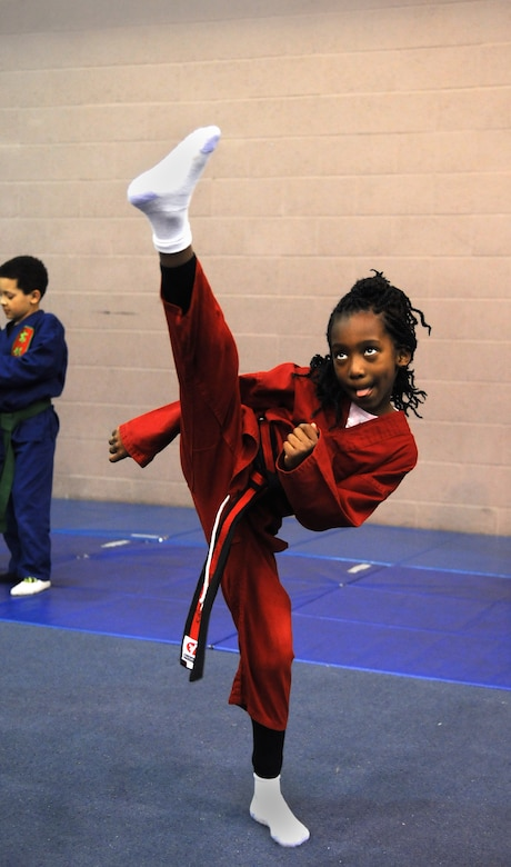 RAF MILDENHALL, England -- Ahmira Palmer performs a high kick during the RAF Mildenhall Youth Center's Karate Camp March 15, 2012. Held monthly, the camp provides the youths an opportunity to practice larger exercises than in the center's normal weekly karate courses. (U.S. Air Force photo/Staff Sgt. Thomas Trower)