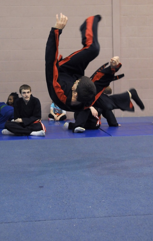 RAF MILDENHALL, England -- Daniel McCollum demonstrates how to flip and safely land on his back during a martial arts demonstration for students of the RAF Mildenhall Youth Center's Karate Camp March 15, 2012. By showing junior students how to fall from greater heights without injury, McCollum can help them build confidence for use during floor exercises. (U.S. Air Force photo/Staff Sgt. Thomas Trower)