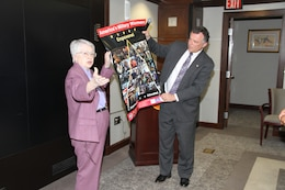 WASHINGTON -- Retired U.S. Air Force Brig. Gen. Wilma L. Vaught presents Dale Stoutenburgh, Director of the U.S. Army Corps of Engineers Humphreys Engineer Center Support Activity, a Women's History Month poster after her keynote speech at the USACE headquarters here, Mar. 26, 2012. Vaught has paved the way for women in the military, but her most lasting contribution is her effort and driving force to build the Women in Military Service for America Memorial, located at Arlington National Cemetery, which honors women who have served in the U.S. military.