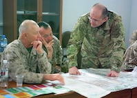 Georgian Lt. Col. Lasha Beridze, Deputy Chief of Joint Staff of the Georgian Armed Forces, shows Lt. Gen. Dennis Hejlik, commanding general of U.S. Marine Corps Forces, Europe (MFE) and Brig. Gen. Chuck Chiarotti, deputy commander of MFE, a map of their current location aboard the Kristani Training Area, located just outside Tbilisi, Georgia, March 24. The U.S. and Georgian leaders met to speak with more than 200 Georgian Armed Forces soldiers from the 23rd Light Infantry Battalion about their upcoming mobilization to Afghanistan, as part of MFE's Georgian Deployment Program – International Security Assistance Force (GDP-ISAF).