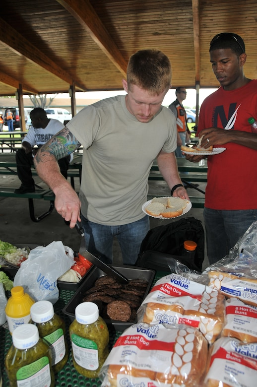 Senior Airman Luke Harshman prepares a burger during the 2012 Joint Base Charleston Motorcycle Safety Event, at Short Stay, the Navy's Outdoor Recreation Area March 23. The event provided motorcyclists with information about safe riding, motorcycle laws in South Carolina, military regulations and proper riding equipment.  Harshman is from the 437th Operations Support Squadron. (U.S. Air Force photo/Airman 1st Class Jared Trimarchi)