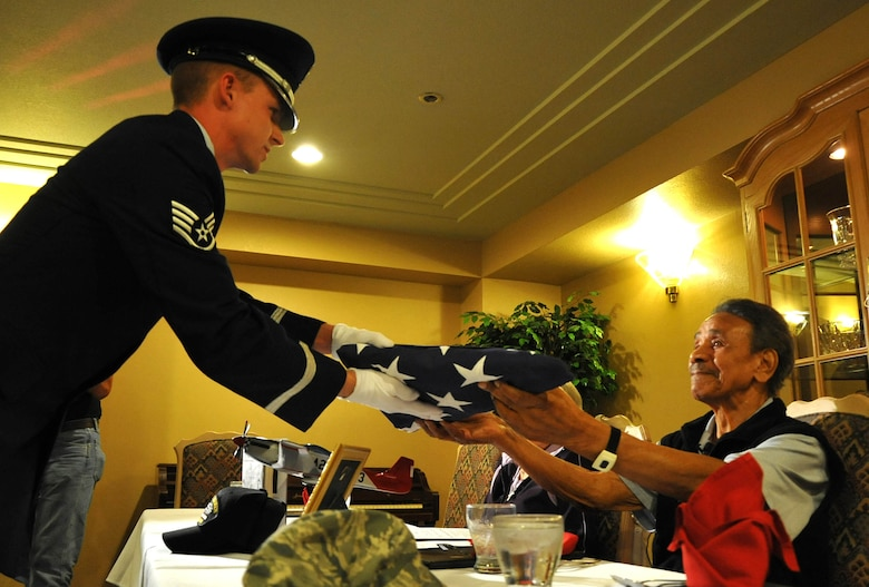 A member of the Davis Monthan Air Force Base Honor Guard presents Mr. Ralph Stewart an American Flag to honor his service in the U.S. Army Air Corps during World War II. Mr. Stewart was a mechanic on the B-25 and B-26 bombers as a Tuskegee Airman. (U.S. Air Force Photo/ Master Sgt. Luke Johnson)