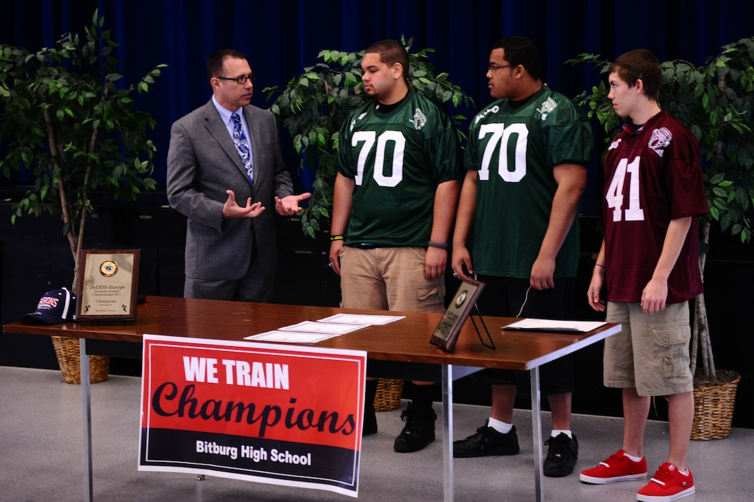 BITBURG ANNEX, Germany – Randy Plunkett, Military.com director of community and government outreach, congratulates, from left, Colton Engelmeier, Darian Billups and Matthew Flood on their selection to the Military.com All-Department of Defense Team at Bitburg High School here March 27. The team is made up of 24 football players who are children of service members stationed throughout the world. Military.com is a military and veteran membership organization that connects service members, military families and veterans to all the benefits of service. The BHS football team members received a certificate and a team jersey, and will attend an upcoming invitation-only 2012 Football University Camp, taught by NFL coaches and players. The team members will find out at a later date which one of the 45 camps they will be invited to attend. (U.S. Air Force photo by Airman 1st Class Matthew B. Fredericks/Released)