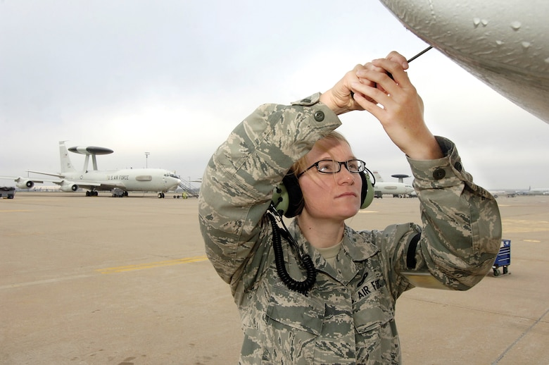 Senior Airman Kelsey Kane is an electronics warfare technician with the 552nd Aircraft Maintenance Squadron used to doing her work in all weather conditions of the E-3 Sentry ramp area at Tinker.  To check connectors of a line replaceable unit, she will remove a panel under the nose of the jet. Air Force photo by Margo Wright)