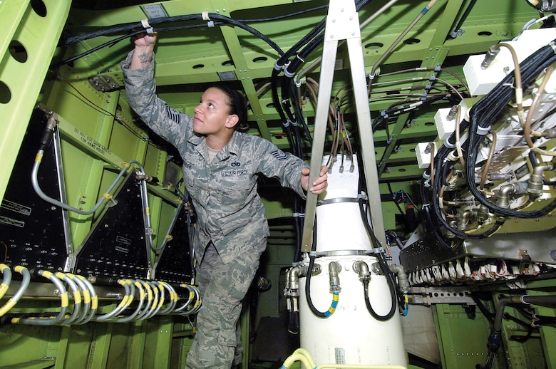 After climbing 30 feet off the ground during a windy day on the aircraft ramp, 5-foot 4-inch tall Tech. Sgt. Lissette Malek tucks herself inside a 30-foot-wide E-3 Sentry rotodome and sets to work ensuring no safety concerns after any rotodome radar maintenance is done. The seven-level inspector, second only to a chief master sergeant nine-level, is a radar technician in the 552nd Maintenance Squadron.  Each AWACS jet is her concern and she'll go from dome to lower lobe areas to ensure a safe flight. (Air Force photos by Margo Wright)
