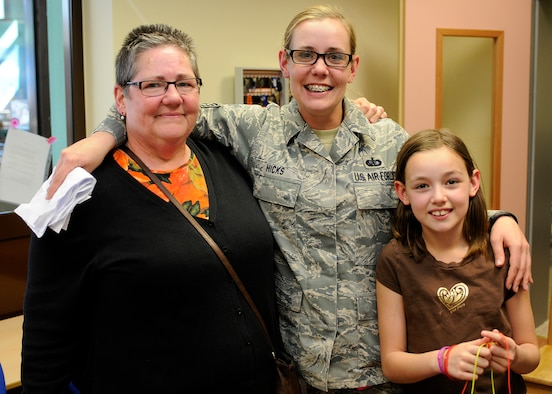 SPANGDAHLEM AIR BASE, Germany – Mother, Constance Besaw; daughter, Staff Sgt. Emma Hicks, 52nd Force Support Squadron; and granddaughter, Zoe Hicks, reunite March 26 at the Spangdahlem School Age Programs building after Hicks returned three weeks early from a deployment to southwest Asia. Besaw works with the base's information, tickets and travel office and stayed with Zoe throughout Hicks' deployment. Hicks convinced the Spangdahlem School Age Programs staff to hold a fake meeting between Besaw and Zoe to discuss cartoon drawings, and Hicks snuck into the room to reunite with her family. (U.S. Air Force photo by Staff Sgt. Daryl Knee/Released)