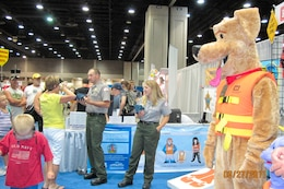 LOUISVILLE, Ky. -- Lake Barkley Park Ranger Charlotte Stenger and U.S. Army Corps of Engineers water safety mascot Bobber the Water Safety Dog speak about inflatable life jackets to Kentucky State Fair visitors here, Aug. 27, 2011.