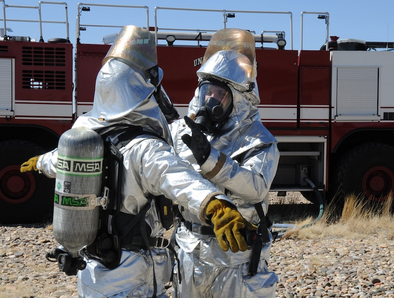 U.S. Air Force firefighters with the 27th Special Operations Civil Engineer Squadron check each other?s fire-resistant gear during a controlled burn at Cannon Air Force Base, N.M., March 15, 2012. Firefighting crews routinely perform exercises like this controlled burn to ensure readiness during an actual disaster. (U.S. Air Force photo by Airman 1st Class Alexxis Pons Abascal)