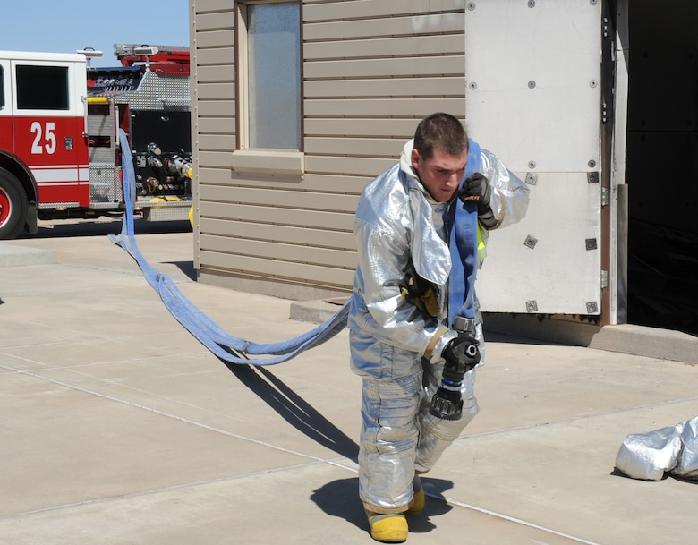A U.S. Air Force firefighter with the 27th Special Operations Civil Engineer Squadron unravels a hose from a nearby fire engine during a controlled burn at Cannon Air Force Base, N.M., March 15, 2012. Firefighting crews routinely perform exercises like this controlled burn to ensure readiness during an actual disaster. (U.S. Air Force photo by Airman 1st Class Alexxis Pons Abascal)