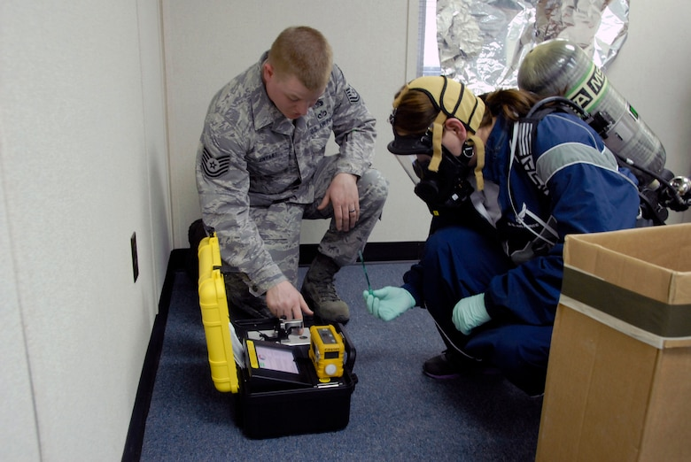 Staff Sgt. Missy Peace, 171st Civil Engineering Emergency Manager, Coraopolis, Pa., trains to use 'HAZ-ID' (Hazardous Material Identifier) equipment in a simulated domestic HazMat scenario at Savannah Combat Readiness Training Center, Savannah, Ga., during Global Guardian 2012, Feb. 16. Staff Sgt. Thomas Enyart, 138th Civil Engineering, Tulsa, Okla., instructs and evaluates Staff Sgt. Peace during the scenario. (ANG Photo By Tech Sgt. Shane P. Hill)