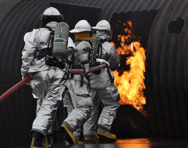 Beale firemen head towards aircraft interior fire during a live fire exercise at Beale Air Force Base, Calif., March 19, 2012. The simulated aircraft is capable of producing different fire scenarios from cockpit fires to cargo bay fires. (U.S. Air Force photo by Staff Sgt. Robert M. Trujillo/Released)