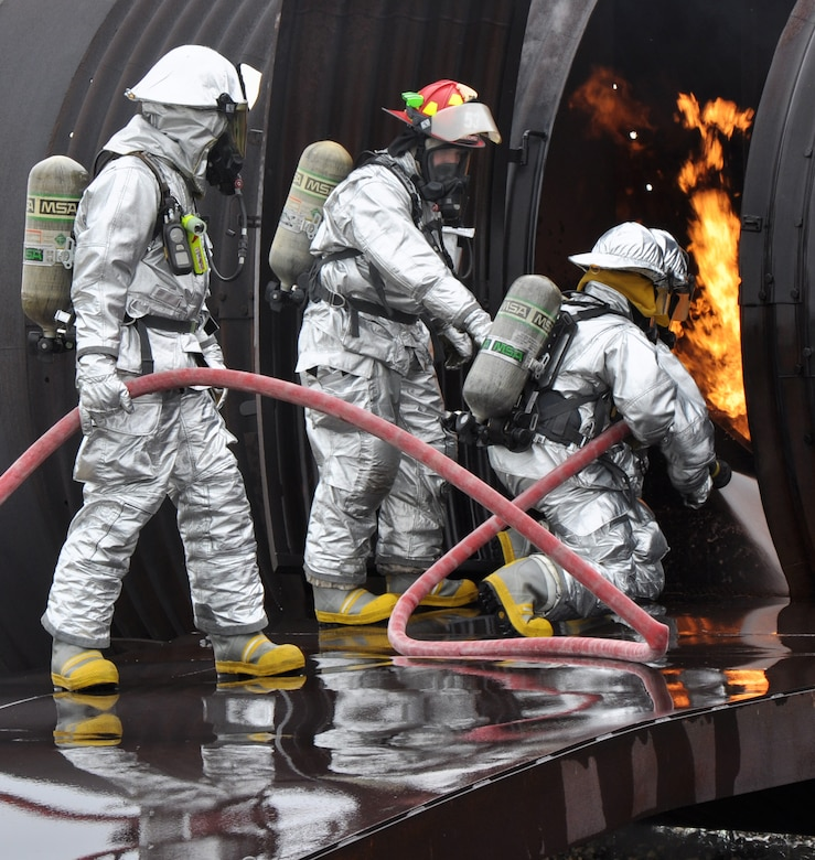 Staff Sgt. Kyle Scritchfield (center), 9th Civil Engineer Squadron fire protection crew chief, guides other Beale firemen at an aircraft interior fire on a simulated aircraft at Beale Air Force Base, Calif., March 19, 2012. Beale firemen routinely utilize the aircraft simulation pit to train at combating aircraft fires. (U.S. Air Force photo by Staff Sgt. Robert M. Trujillo/Released)