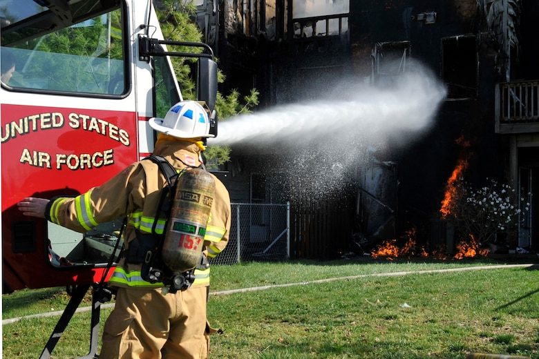 11th Civil Engineer Squadron firefighters use the bumper turret on an Aircraft Rescue and Firefighter truck to extinguish a house fire here March 29. Firefighters from the 11 CES and two stations in Prince George's County fought the blaze that ended up in multiple damaged homes. (U.S. Air Force photo/Senior Airman Perry Aston)