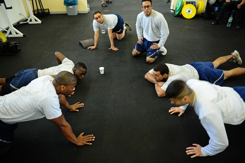 SPANGDAHLEM AIR BASE, Germany – Members of the 52nd Component Maintenance Squadron watch teammate Staff Sgt. Brandon Bertrand, bottom right, 52nd CMS, do pushups during the Iron Flight Competition at the Combat Fitness Center here March 28. The quarterly competition is an incentive program intended to build comraderie and test the mental and physical endurance of the participating squadron members. Four teams participated in the six-person team competition that consisted of three different events. The 52nd Equipment Maintenance Squadron ammo team won the competition after a three-way tie-breaker rope-climbing event against the 52nd Civil Engineer Squadron and CMS. (U.S. Air Force photo by Airman 1st Class Matthew B. Fredericks/Released)