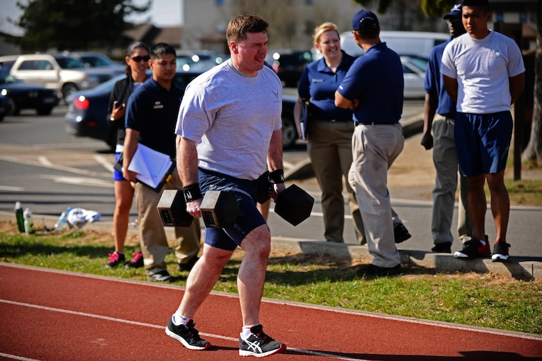 SPANGDAHLEM AIR BASE, Germany – Master Sgt. Carlos Crasta, 52nd Component Maintenance Squadron, runs while holding two 85 pound dumbbells during the Iron Flight Competition at the track here March 28. The quarterly competition is an incentive program intended to build comraderie and test the mental and physical endurance of the participating squadron members. Four teams participated in the six-person team competition that consisted of three different events. The 52nd Equipment Maintenance Squadron ammo team won the competition after a three-way tie-breaker rope-climbing event against the 52nd Civil Engineer Squadron and CMS. (U.S. Air Force photo by Airman 1st Class Matthew B. Fredericks/Released)