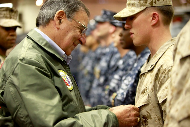 Secretary of Defense Leon Panetta pins a Navy and Marine Corps Commendation Medal on Lance Cpl. Christophe C. Cowley, an assault leader with Kilo Company, Battalion Landing Team 3/5, 15th Marine Expeditionary Unit, today. Cowley was awarded the medal for his actions in combat on 3/5's last deployment. During his visit, Panetta toured the ship, had lunch with Marines and sailors, pinned awards on several service members, and held a brief press conference with the media. Panetta came to visit the Marines and sailors to reinforce his commitment to maintaining an expeditionary fighting force.