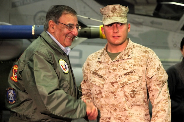 Secretary of Defense Leon Panetta presents a challenge coin to Pfc. Aryan A. Szczurowski, a rifleman with Lima Company, Battalion Landing Team 3/5, 15th Marine Expeditionary Unit, today. During his visit, Panetta toured the ship, had lunch with Marines and sailors, pinned awards on several service members, and held a brief press conference with the media. Panetta came to visit the Marines and sailors to reinforce his commitment to maintaining an expeditionary fighting force.
