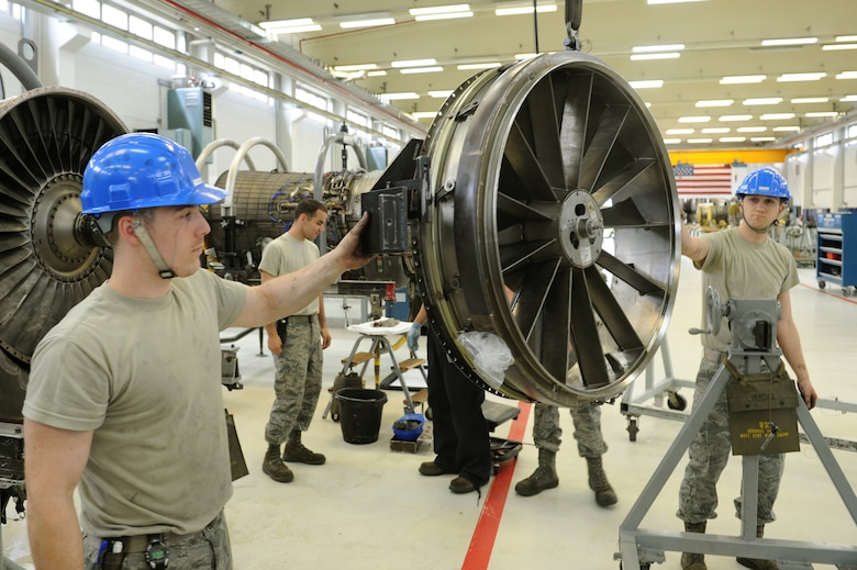 SPANGDAHLEM AIR BASE, Germany – Senior Airman Willis Jenson, left, and Senior Airman Braden Duke, 52nd Component Maintenance Squadron aerospace propulsion technicians, guide the front frame from of F-16 Fighting Falcon turbine to a disassembly stand during the removal of all moving parts of the engine at Bldg. 73 here April 30. Technicians replace these moving parts in a turbine every 4,000 flight hours as required by the service life extension program. CMS provides maintenance support to the 52nd Fighter Wing, the 31st FW at Aviano AB, Italy, and all U.S. F-16 units powered by F-110 engines in the European theater and deployed locations. (U.S. Air Force photo by Senior Airman Christopher Toon/Released)