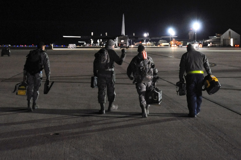 Crew chiefs from the 27th Special Operations Aircraft Maintenance Squadron carry their tools to the AC-130H Spectre gunship as they prepare for a nightly inspection of the aircraft.  Many squadrons, such as the 27 SOAMS are operational 24/7 to keep aircraft in the air no matter what time it is.  (U.S. Air Force photo by Senior Airman Jette Carr)