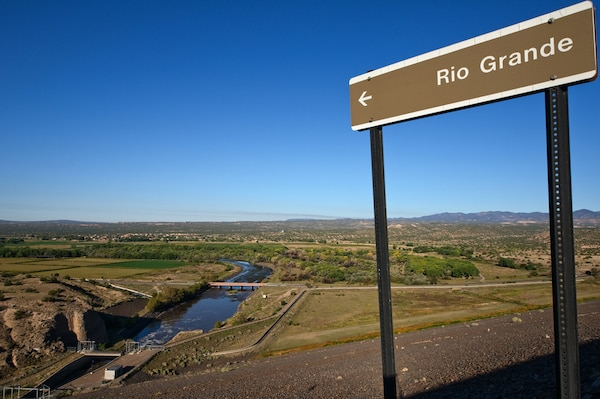 A sign stands atop the Cochiti Lake Dam that points to the Rio Grande below.