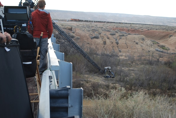 The film crew set up a crane with a camera to take imagery of action taking place under a bridge along the Rio Puerco river.