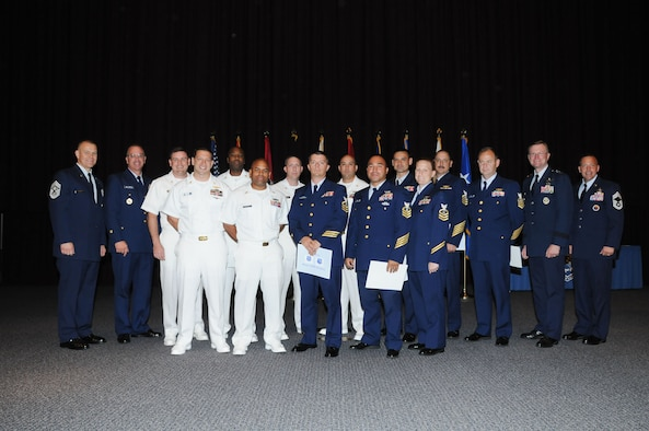 From left, Chief Master Sergeant of the Air Force James Roy is joined by his counterpart, Master Chief Petty Officer of the Coast Guard Michael Leavitt with graduates of the Air Force Senior NCO Academy Tuesday. Featured second from right is Lt. Gen. David Fadok, commander and president of the Air University. Air Force photo by Bud Hancock