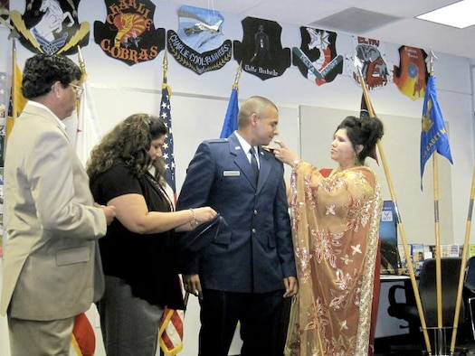 Members of 2nd Lt. Jason Ram's family pin on his second lieutenant bars at his commissioning at Loyola Marymount University, August 26, 2011.  Lieutenant Ram is currently stationed with the 479th Flying Training Group at Naval Air Station Pensacola, Fla.  The 479th FTG is the 12th Flying Training Wing's geographically separated unit and conducts Combat Systems Officer Training for the U.S. Air Force.  (Courtesy Photo)