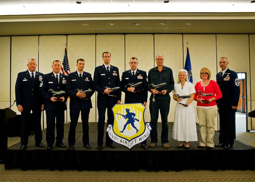 (Left to Right) Col. Erik Hansen, Master Sgt. Rene Delarosa, 1st Lt. Edward Yerage, Capt. Benjamin Wood, Tech. Sgt. Matthew Ancell, Randall Gillum, Tamra Fuchs and Kayle Ealey pose at the conclusion of the 437th Airlift Wing Quarterly Awards ceremony at Joint Base Charleston - Air Base April 27. Hansen is the 437th AW commander, Delarosa is a 15th Airlift Squadron loadmaster superintendent, Yerage is a 437th Aerial Port Squadron ramp operations flight commander, Wood is a 17th Airlilft Squadron chief of tactics and instructor aircraft commander, Ancell is a 437th Maintenance Group quality assurance inspector, Gillum is a 437th Maintenance Squadron machinist and Fuchs is a 437th MXS command section administrator. Kayle Ealey accepted the award for her husband Airman 1st Class Robert Ealey, 437th APS special handling apprentice, and Williams is the 437th AW command chief. (U.S. Air Force photo/Airman 1st Class George Goslin)