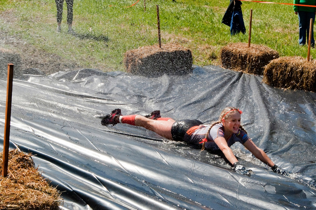 MANCHESTER, N.H. -- Tech. Sgt. Jessie Davidson slides down the final obstacle during the Adventure 5k at McIntyre Ski area April 28. Davidson and ten others from the New Hampshire Air National Guard participated as a team called Obstacle Illusion. More than 800 participants ran through mud trails and over obstacles during the 3.1 mile event. (National Guard photo by Tech. Sgt. Mark Wyatt/Released)