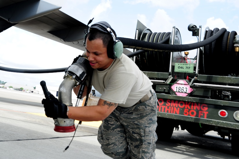 Senior Airman Rafael Lopez-Martinez pulls the hose towards a C-17 Globemaster III before refueling, at Joint Base Charleston - Air base, April 18. The C-17 can hold up to 35,546 gallons of fuel and can carry a maximum of 17,900 pounds and land on runways as short as 3,500 feet which is crucial to resupplying remote areas from the air or ground. Lopez-Martinez is from the 437 Aircraft Maintenance Squadron Gold AMU.  (U.S. Air Force photo/ Staff Sgt. Nicole Mickle)