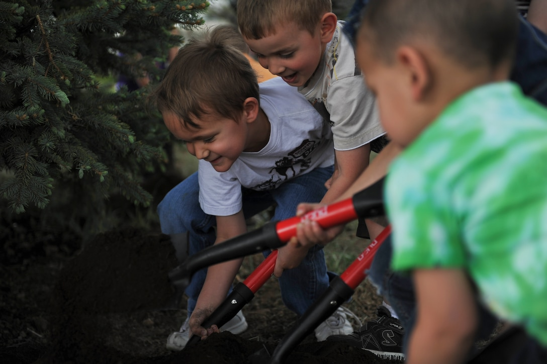BUCKLEY AIR FORCE BASE, Colo. – Tristan Rowley, left, and Aaron Diggs, middle, from the Buckley Child Development Center plant and take care of trees, April 26, 2012. It was the lack of trees in Nebraska that led to the founding of Arbor Day in the 1800's. (U.S. Air Force photo by Airman 1st Class Darryl Bolden Jr.)