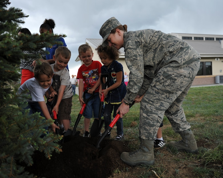 BUCKLEY AIR FORCE BASE, Colo. – Col. Tracey Hayes, 460th Space Wing vice commander, helps children plant a tree for Arbor Day, April 26, 2012. The Buckley Child Development Center and Buckley leadership helped raise awareness for the environment. (U.S. Air Force photo by Airman 1st Class Darryl Bolden Jr.)
