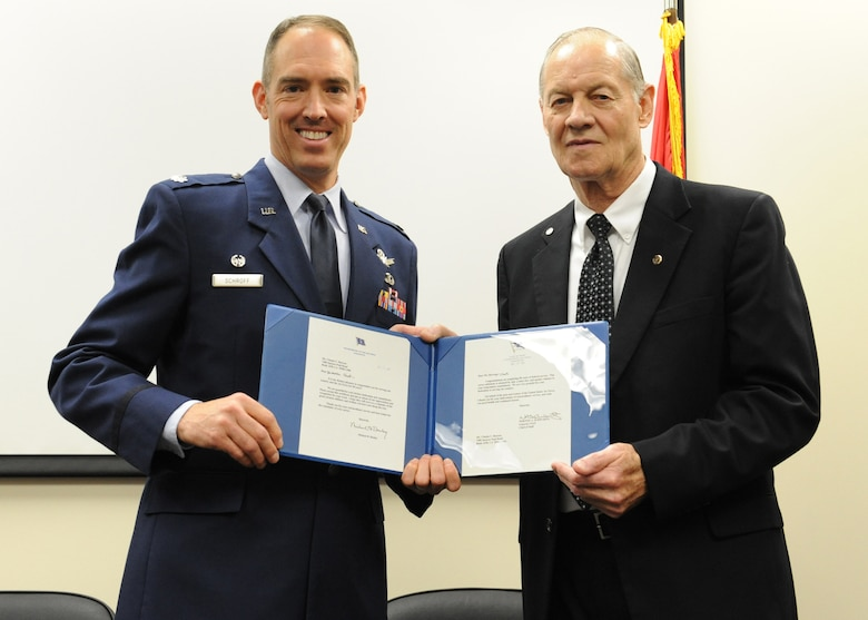 Lt. Col. Scott Schroff, 7th Space Warning Squadron commander, presents Chet Burress, 7th SWS ground radar systems analyst, letters from the Chief of Staff of the Air Force, Gen. Norton A. Schwartz and Chief Master Sgt. of the Air Force James A. Roy at a ceremony April 26 at Beale Air Force Base, Calif. Burress received numerous awards for his 50 years of federal service. (U.S. Air Force photo by Mr. John Schwab)